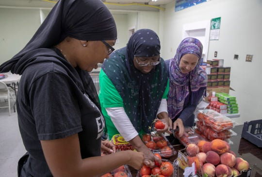 Volunteers weed out a few suspect tomatoes as they get ready for a food pantry at Masjid Al Mumineen, Indianapolis, Aug. 25, 2018. The Masjid's monthly pantry runs from 1-3 on the last Saturday of the month and serves anybody who needs food, which has been donated by Gleaner's, plus other area Majids and private citizens.
