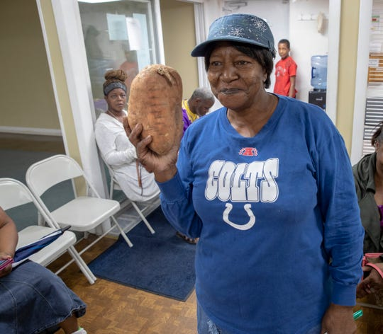 Thelma Gammon, a Christian who lives near Masjid Al Mumineen, holds up one of the enormous sweet potatoes that will be given out on food pantry day at the Masjid, Indianapolis, Aug. 25, 2018. The Masjid's monthly pantry runs from 1-3 on the last Saturday of the month and serves anybody who needs food, which has been donated by Gleaner's, plus other area Majids and private citizens.