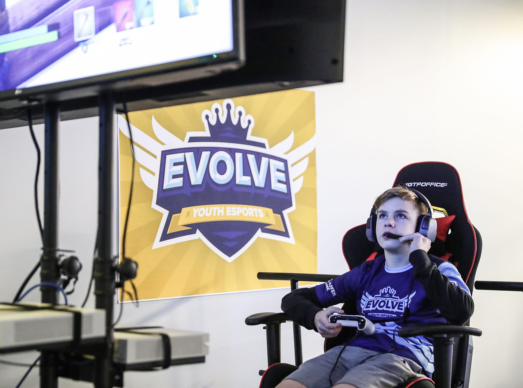 Brandon Woodard, 14, communicates through a headset during an Evolve Youth Sports practice at the Player One arena in Carmel, Ind., Thursday, Jan. 24, 2019. Scott Wise, original founder of Scotty's Brewhouse, has partnered with Player One Esports for his next venture, a video game sports league that has attracted around 200 kids so far.