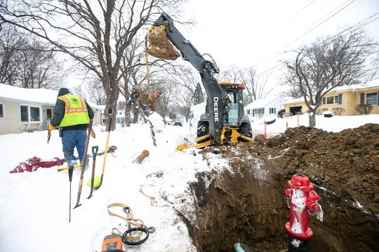 Iowa City Water Distribution employees work to fix a broken fire hydrant on Monday, Jan. 28, 2019, along Morningside Drive on the corner of Court Street in Iowa City, Iowa. Water was temporarily disconnected to the street while crews finished repairs.