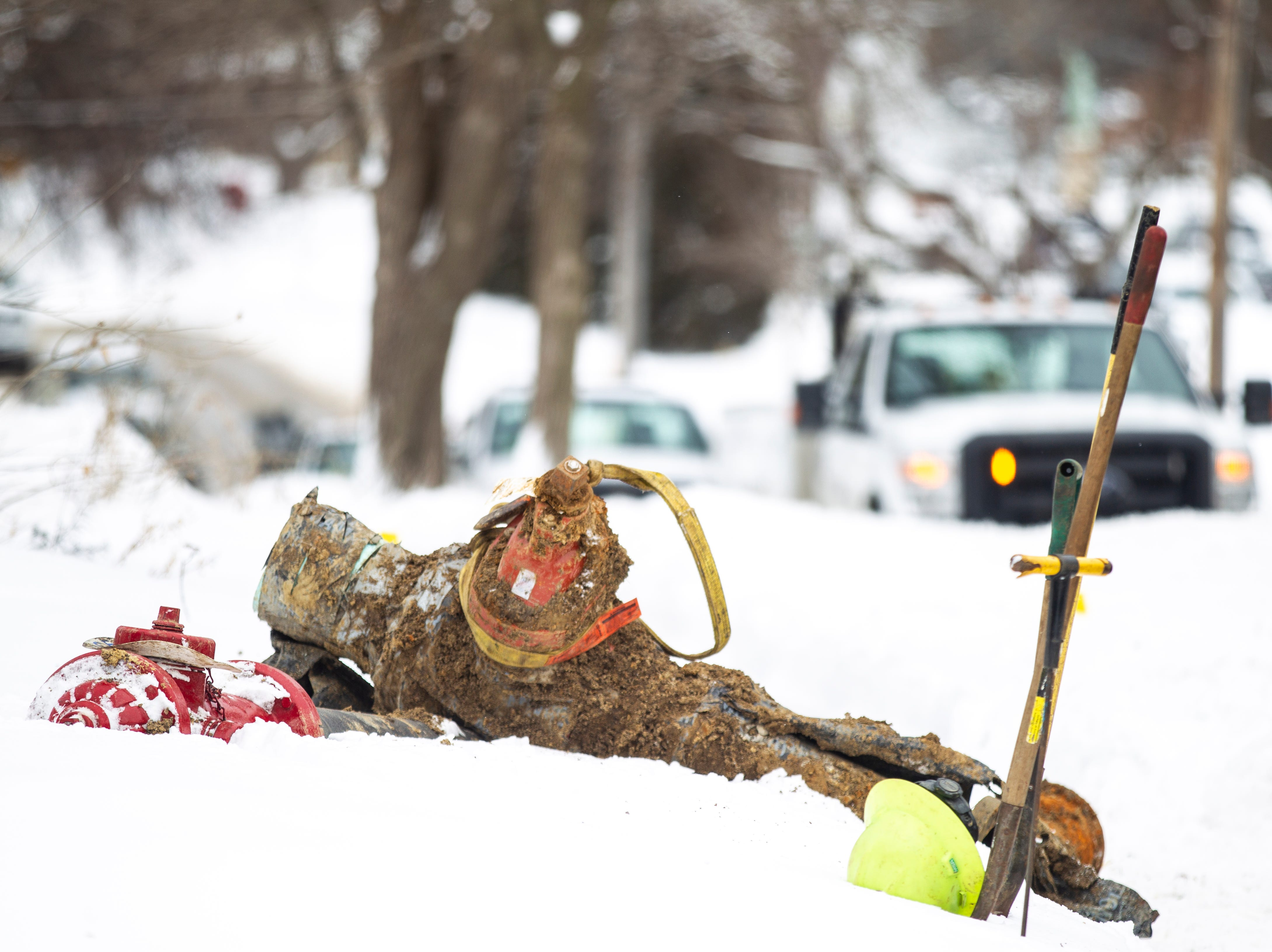 Iowa City Water Distribution employees work to fix a broken fire hydrant on Monday, Jan. 28, 2019, along Morningside Drive on the corner of Court Street in Iowa City, Iowa.