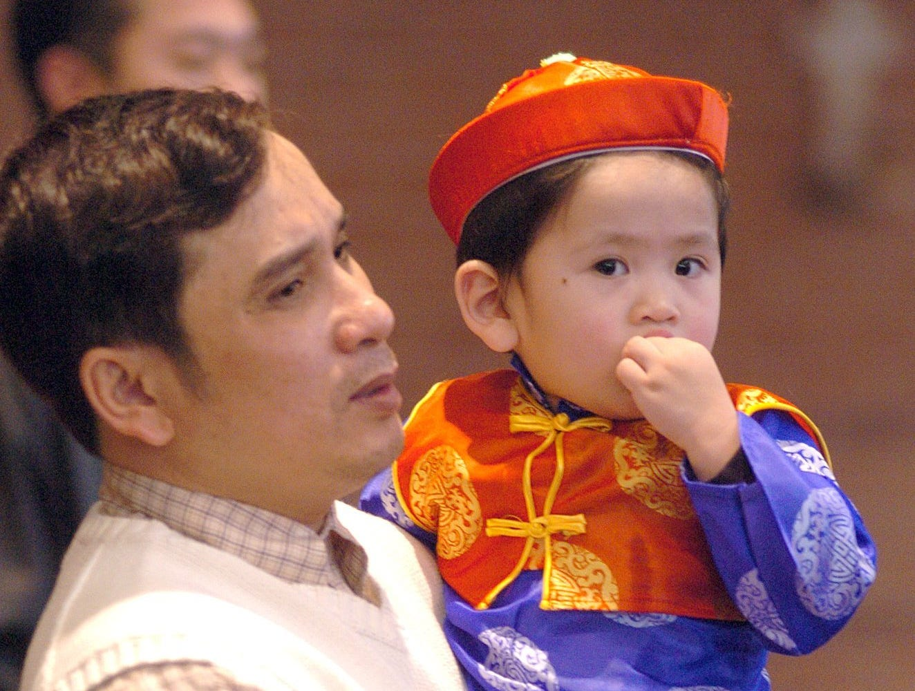 Dung Tran holds son Robert Nguyen, 2, during a mass for members of the Vietnamese community to celebrate the Chinese New Year at the St. Therese Catholic Church in Jackson. At a reception following the service, church members ate, sang and performed a traditional dragon dance.