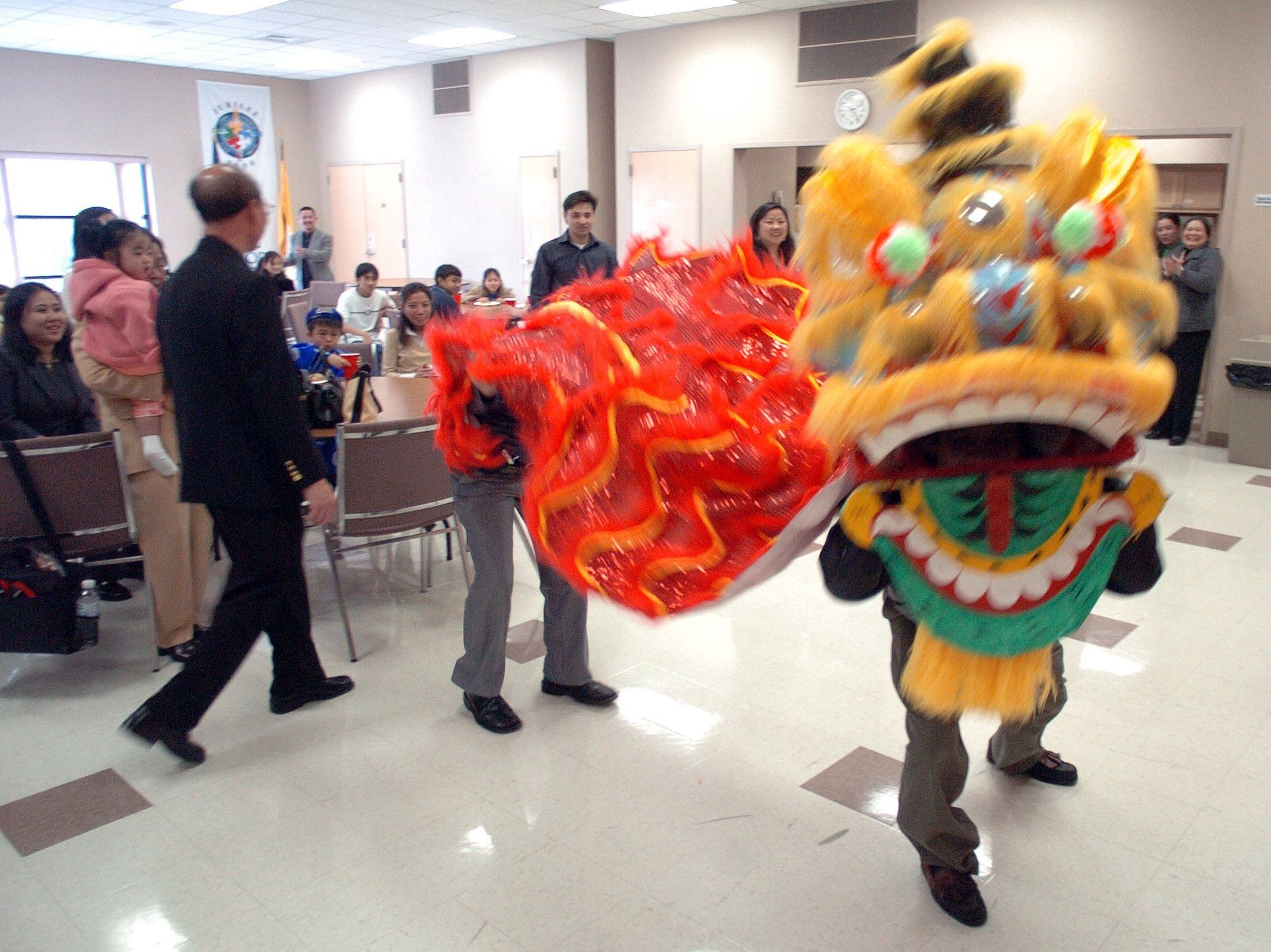 As part of a celebtration of Chinese New year, Elton Nguyen (right), 11, plays a drum as Luong Nguyen (front) and Thomas Le perform a traditional dragon dance at a reception following a mass at the St. Therese Catholic Church in Jackson for members of the Vietnamese community.