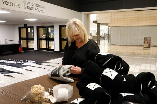 Kandy Barr folds shirts with the new X Church logo on them Tuesday, Jan. 24, 2019, at River Valley Mall in Lancaster. Barr, who attends the church's Lancaster campus, stopped by after work to see if the staff needed help preparing for Sunday's service after the announcement of the name change from Crossroads.TV to X Church.