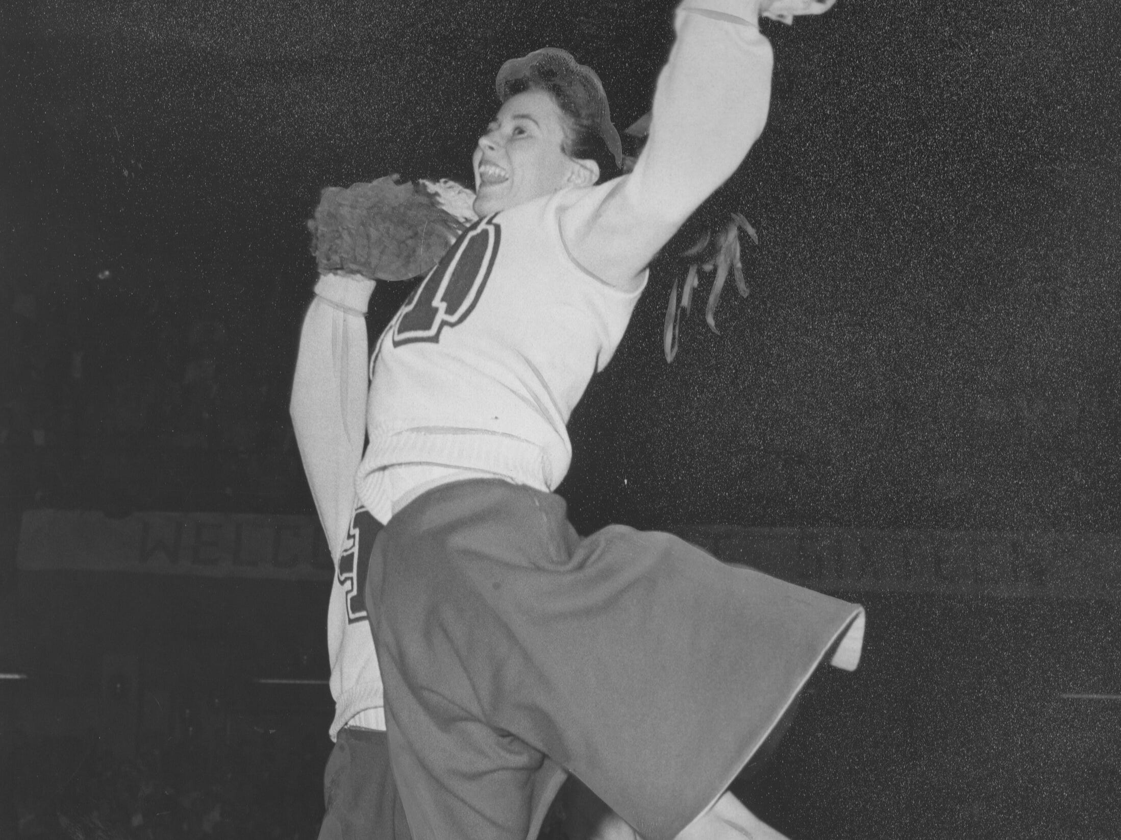 Manual cheerleader Ruthie Aldridge leaps his during a game against Central City.March 19, 1959