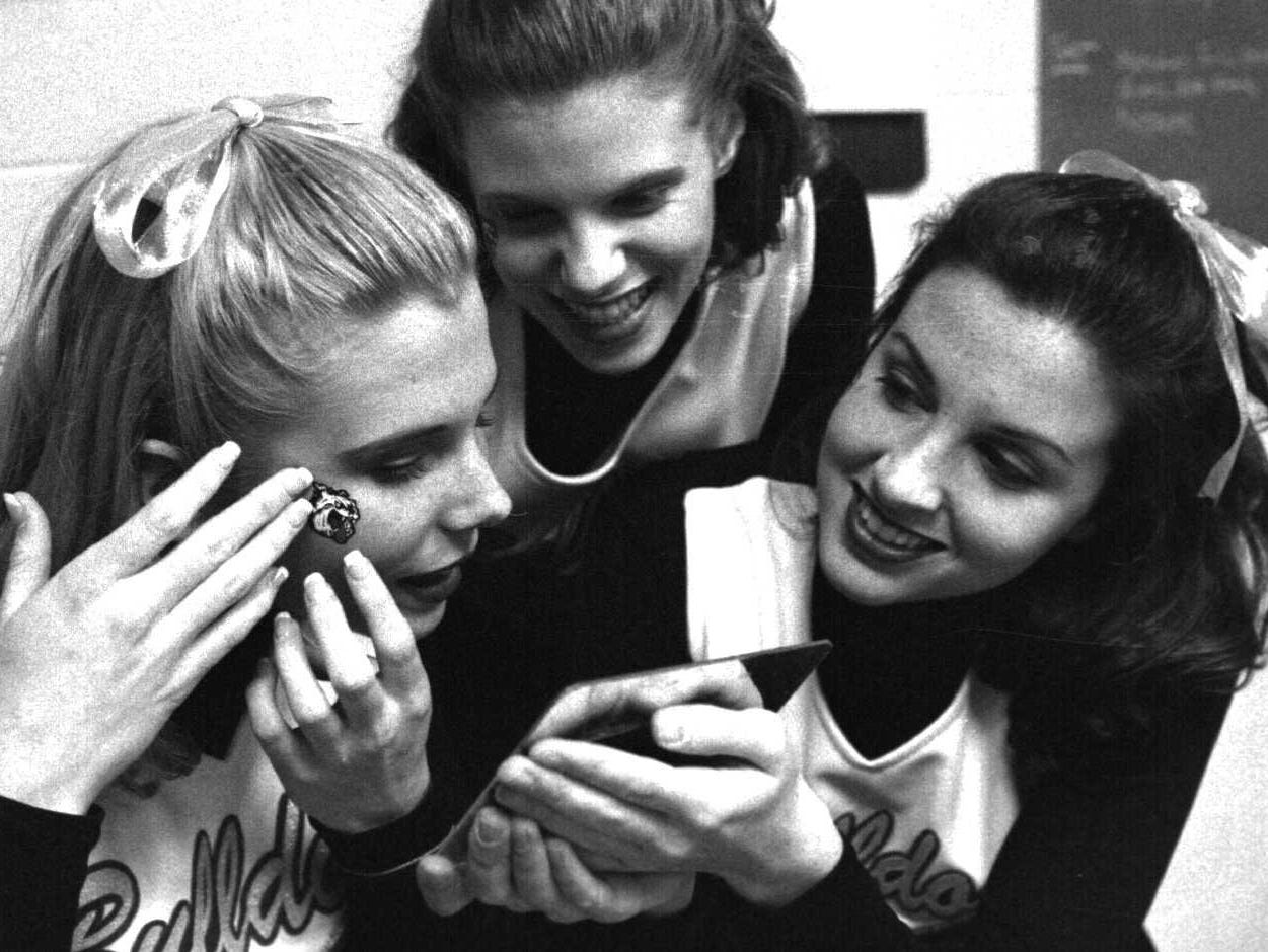 """Floyd Central at New Albany, left to right, New Albany Cheerleaders- Ruthie LaDuke (SR) Celia Bauer (Soph) Jennifer Kasse (SR) putting on """"Bulldog Face"""" fake tattoo- Pre Game.  12/13/96"""
