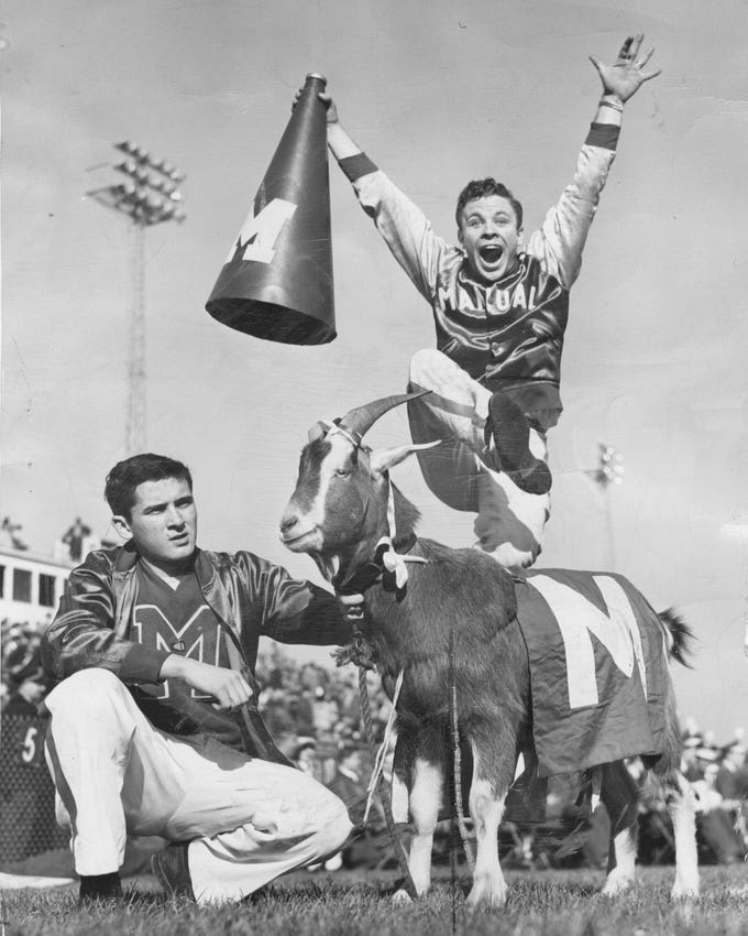 Manual of Louisville usually produces a goat to inspire its footballers, the Maroons, on Thanksgiving Day games. This 1946 photo shows one being held by Eddie Wyatt. William Marcum is doing all that leaping. Nov. 29, 1946