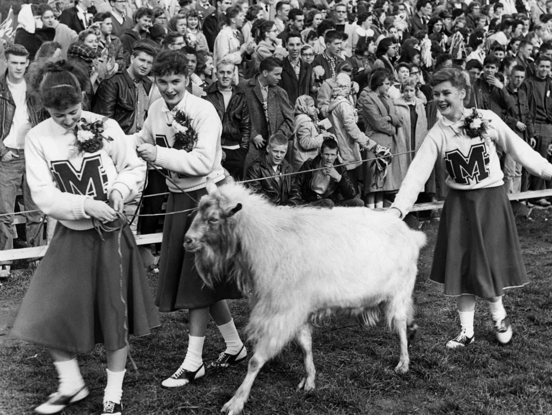 Manual cheerleaders Ruthie Aldridge, left, Norma Catinna, center, and at right, Wilma Horn, guided the mascot to its observation spot.Nov. 28, 1957
