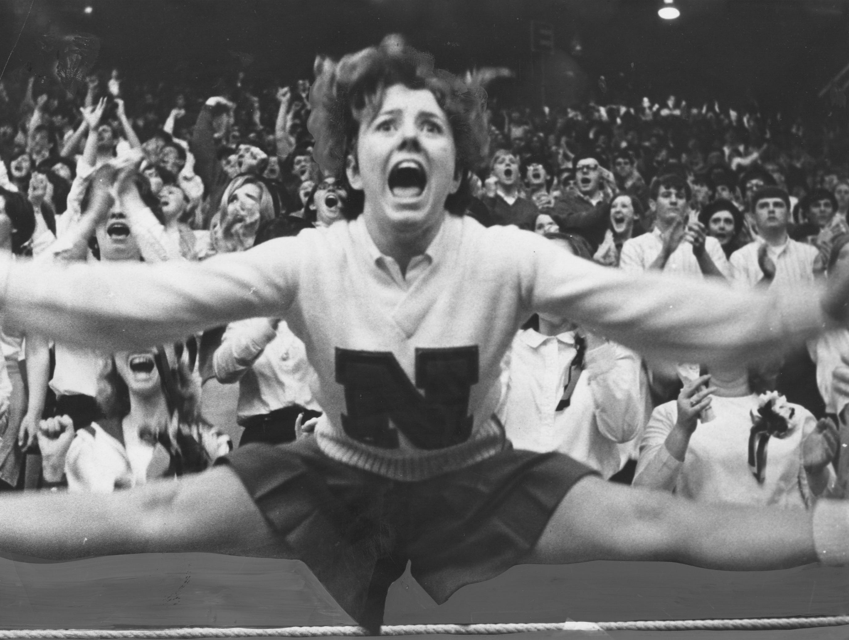 Cheerleader Brenda Sullivan goes all out to show her enthusiasm while striking up some vocal backing for New Albany's Bulldogs in yesterday's afternoon's battle with North High School. March 12, 1967