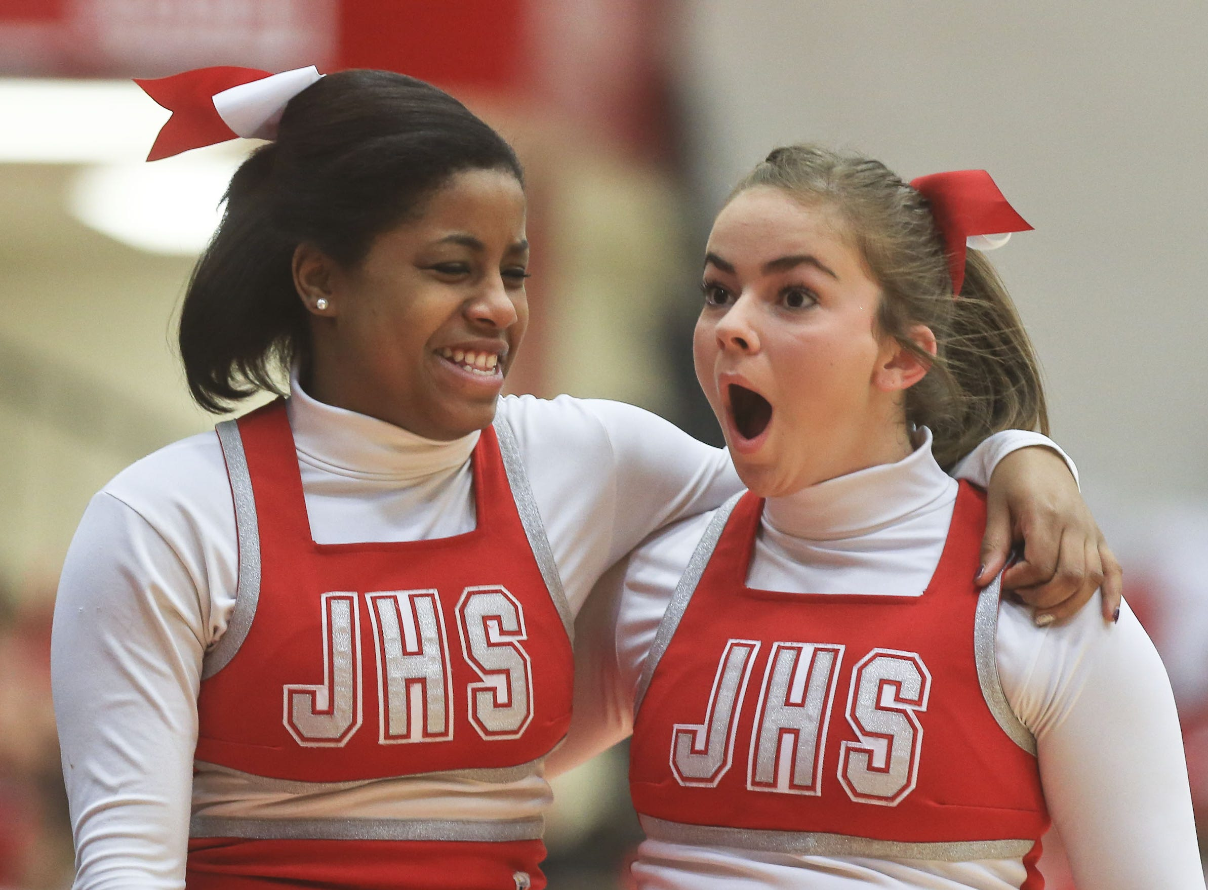Jeff High cheerleaders Breanna Martin, left, and Lyndzy Obremski share a joke before the game against Trinity Tuesday night in Jeffersonville.