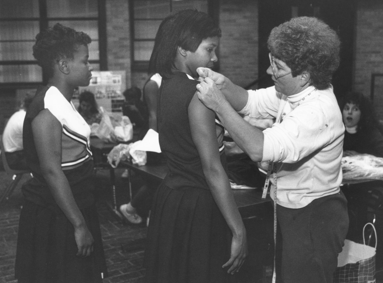 Tina Strange, right, adjusts a new uniform on Central High School cheerleader Tia Mewby, center, as Ja Quan Jackson waits. Nov. 11, 1992
