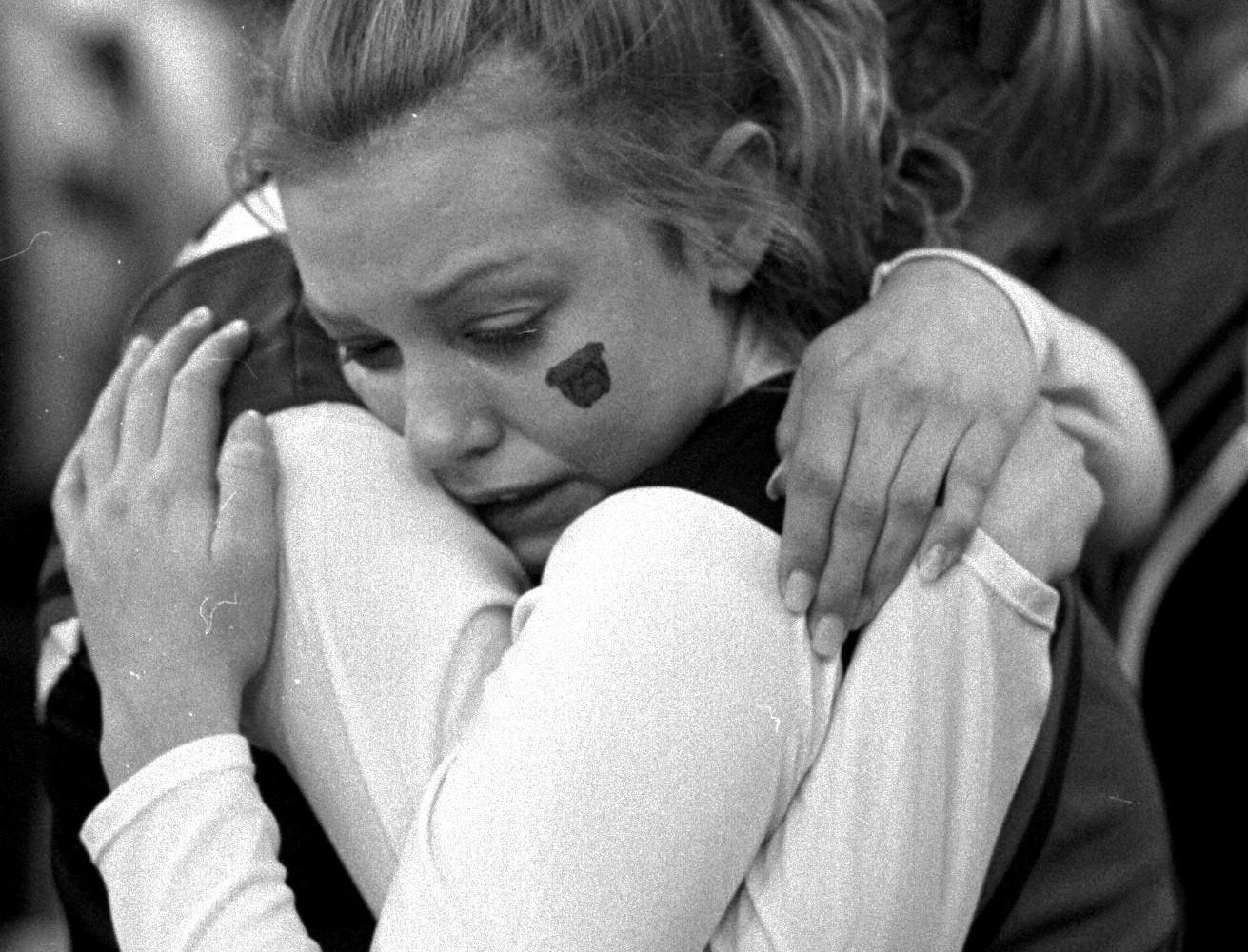Cheerleaders Brooklyn Farris, facing, and Ruthie LaDuke comforted each other after the Bulldogs lost on a last-second three-pointer. Below, Leslie Sauer and Bobby Cunningham yelled during the game.March 24,1996.