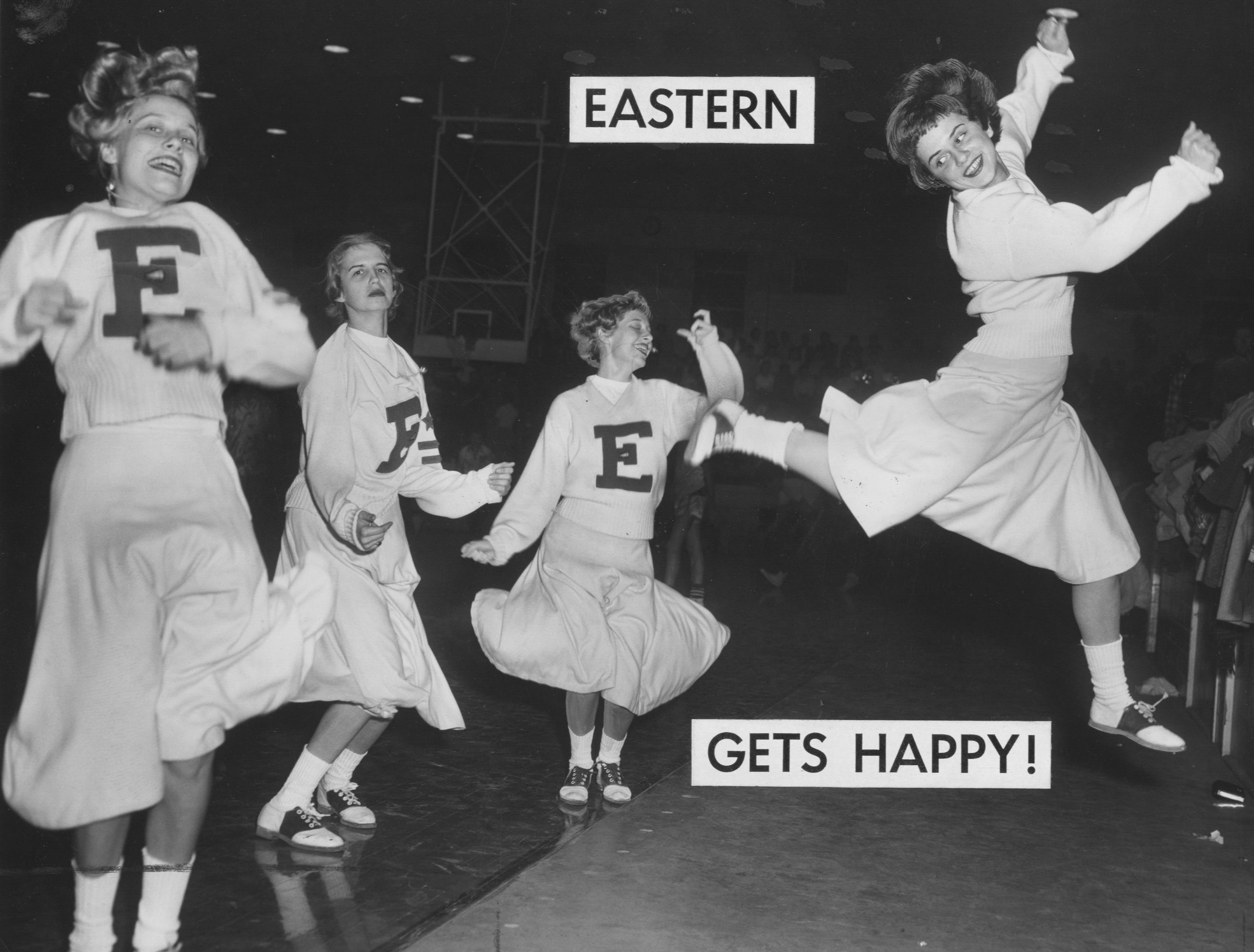 Two of Eastern High School cheerleaders give out with enthusiasm during the Eagle's battle with Manual. Jan. 11, 1957