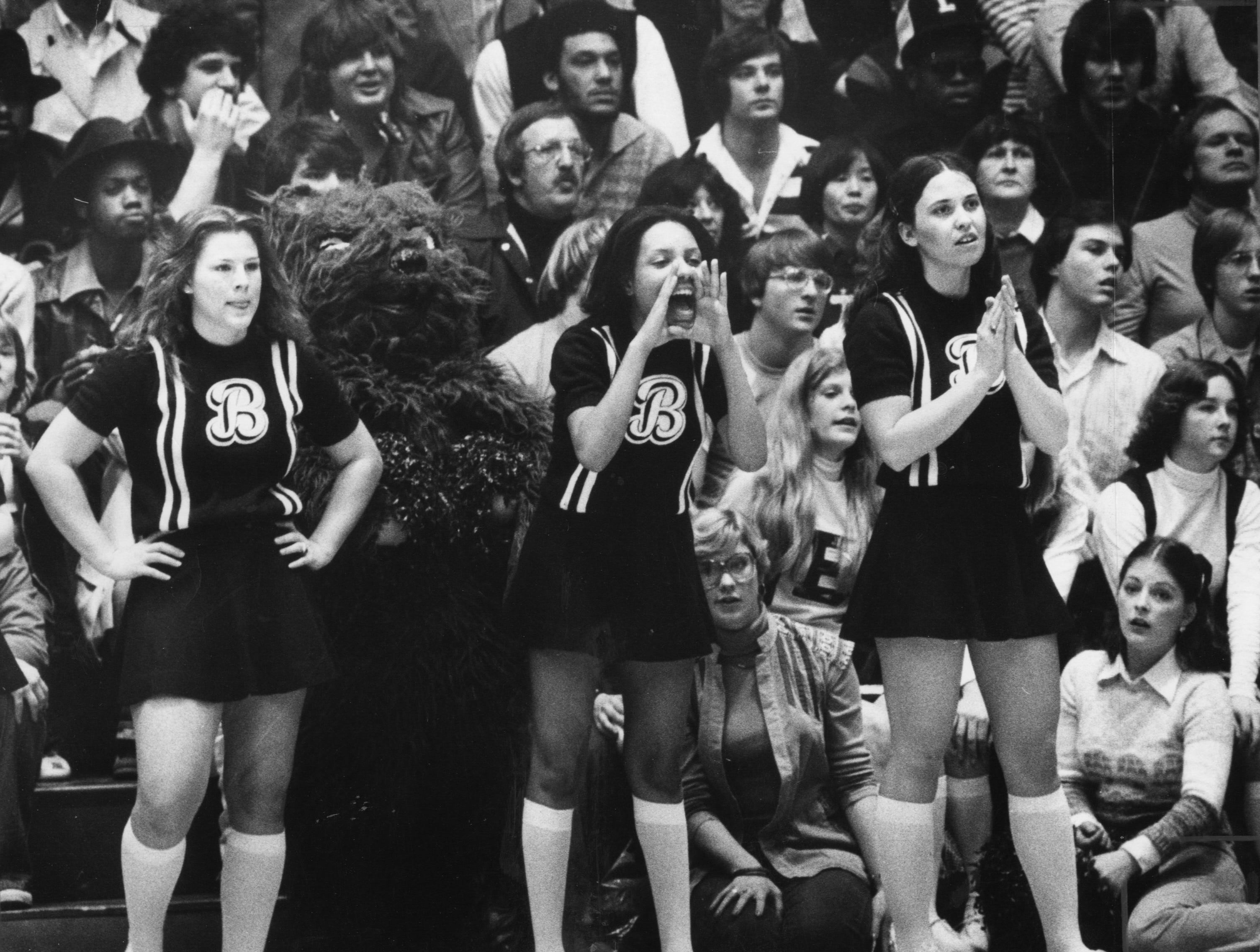 Ballard cheerleaders (from left) Ann Higgins, Suzanne Keller and Melissa Summer cheer on their team against Jeffersonville. Feb. 5, 1977