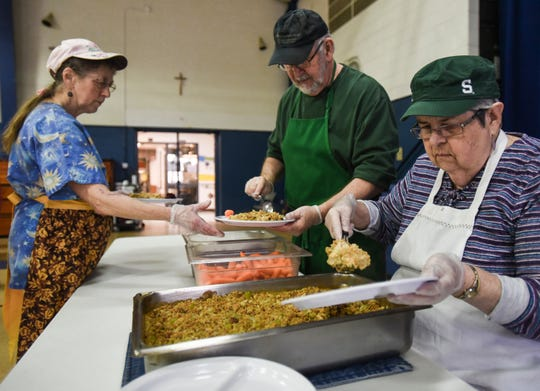 From left, Southside Community Kitchen volunteers Kim Gools, Mike Swartz, and Nina Machtel, all of Lansing, prepare plates of food to deliver to guests, Wednesday, Jan. 16, 2019, at St. Casimir Church in Lansing.