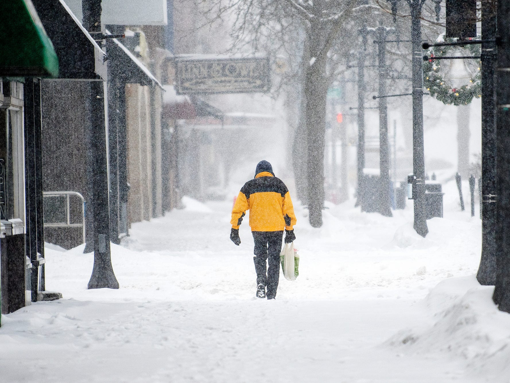 A pedestrian walks through the snow on Washington Square on Monday, Jan. 28, 2019, in Lansing. A major snow storm hit the region Monday and will be followed by days of bitter, life-threatening cold.