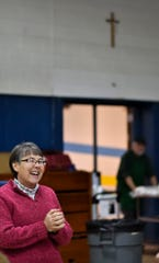 Marcia Beer, director of the Southside Community Kitchen, laughs with lunch guests after giving thanks, Wednesday, Jan. 16, 2019, at St. Casimir Church in Lansing.  They serve 1,200 to 1,300 meals per month.