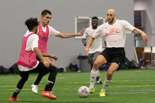 Lansing city councilman Brian Jackson advances the ball in traffic during the Lansing Ignite open tryouts Sunday, Jan. 27, 2019 in Brighton.