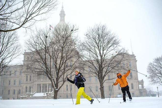 Patty Sutherland, left, and Dwight Washington cross country ski in front of the Michigan State Capitol on Monday, Jan. 28, 2019, in Lansing. The two, who were out enjoying the weather, wanted to ski down Michigan Avenue to the Capitol. A major snow storm hit the region Monday and will be followed by days of bitter, life-threatening cold.