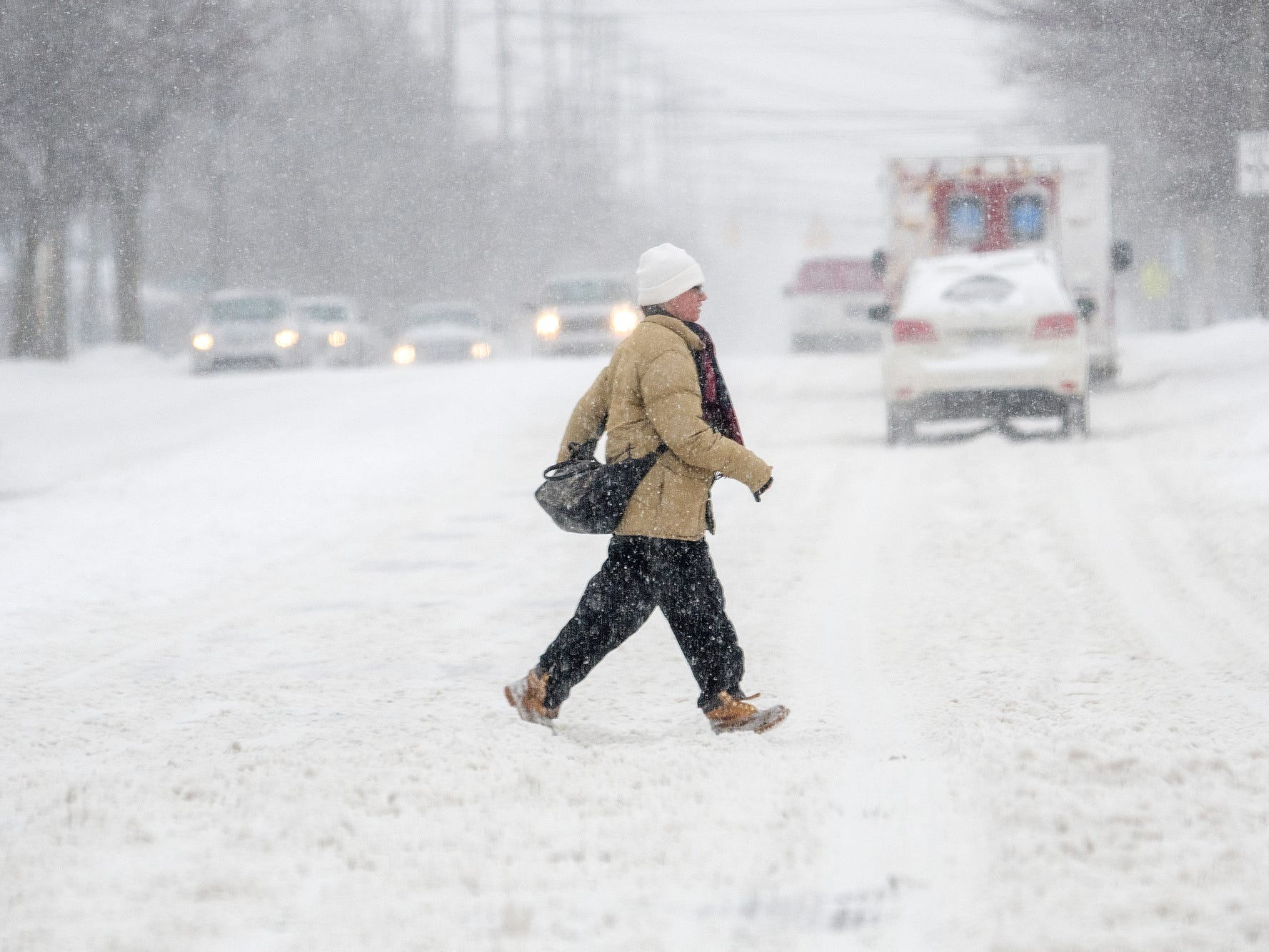 A pedestrian crosses Pennsylvania Avenue along Michigan Avenue on Monday, Jan. 28, 2019, in Lansing. A major snow storm hit the region Monday and will be followed by days of bitter, life-threatening cold.
