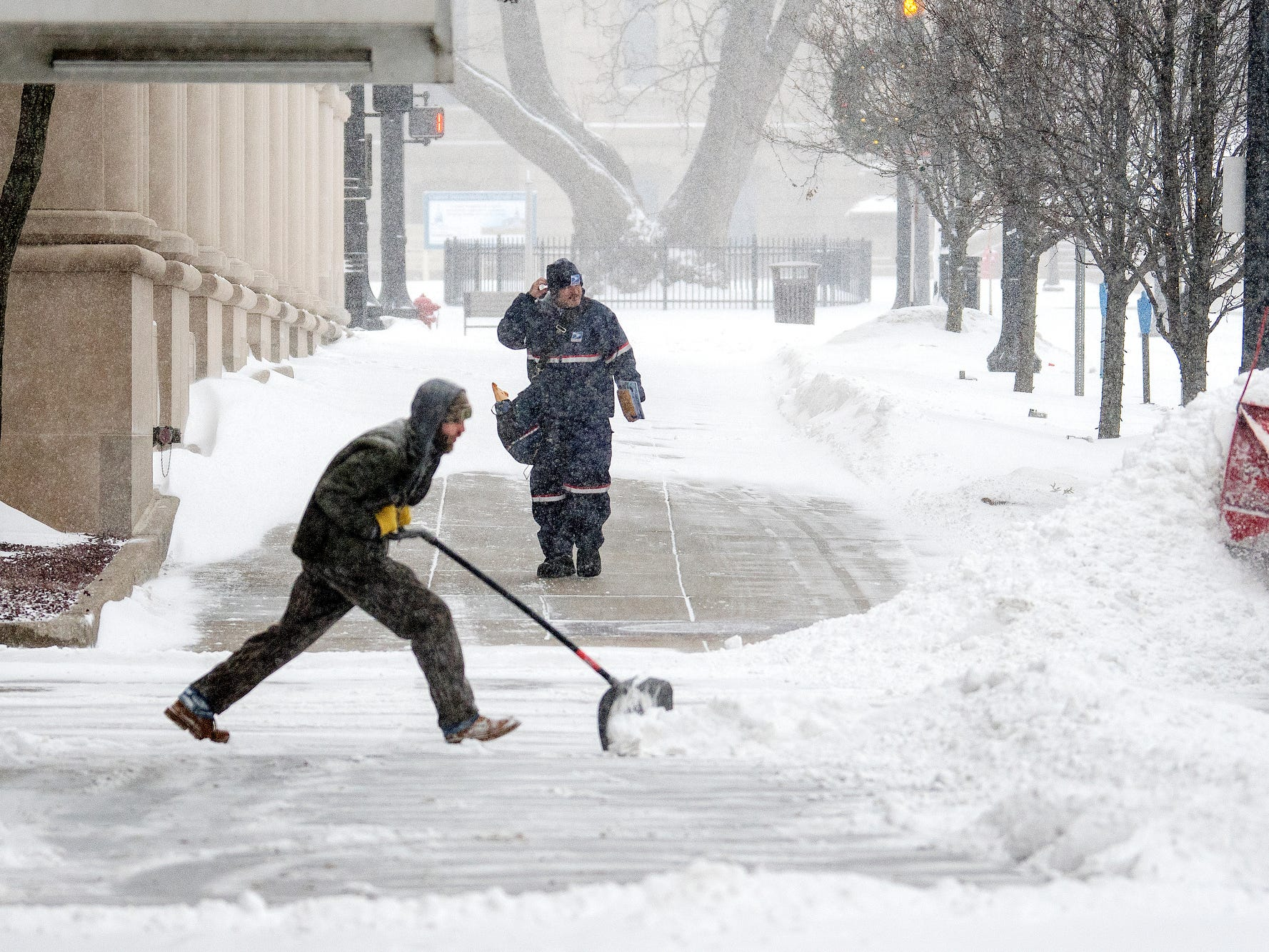 A postal worker, center, walks along Michigan Avenue near the Capitol Avenue on Monday, Jan. 28, 2019, in Lansing. A major snow storm hit the region Monday and will be followed by days of bitter, life-threatening cold. The postal service suspended delivery of mail on Wednesday due to cold temperatures.