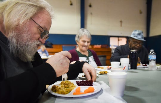 Lawrence McDaniel of Lansing, left, eats lunch with Patricia and Joseph Weems and others at the Southside Community Kitchen at St. Casimir's in Lansing, Wednesday, Jan. 16, 2019.