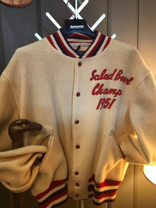 Al Ward's varsity jacket as a member of Woody Hayes' 1950 Miami of Ohio football team that won the Mid-American Conference championship and the Jan. 1 Salad Bowl (now the Fiesta Bowl) over Arizona State. Tucked inside the sleeve of the coat is a walking cane carved by Ward.