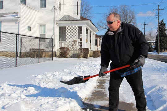 Kevin McKinney shovels the sidewalk outside his home Sunday on Silver Street. The National Weather Service forecasts high winds in the area allowing for wind chills of 25 to 35 degrees below zero this week.