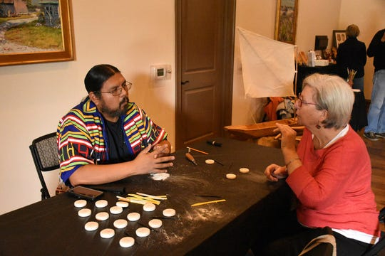 Seminole historian Pedro Zepeda demonstrates traditional carving on bars of soap to Nazare Hamilton. The return of the Key Marco Cat and associated artifacts became offical Saturday, with a celebration and ribbon cutting held at the Marco Island Historical Museum.