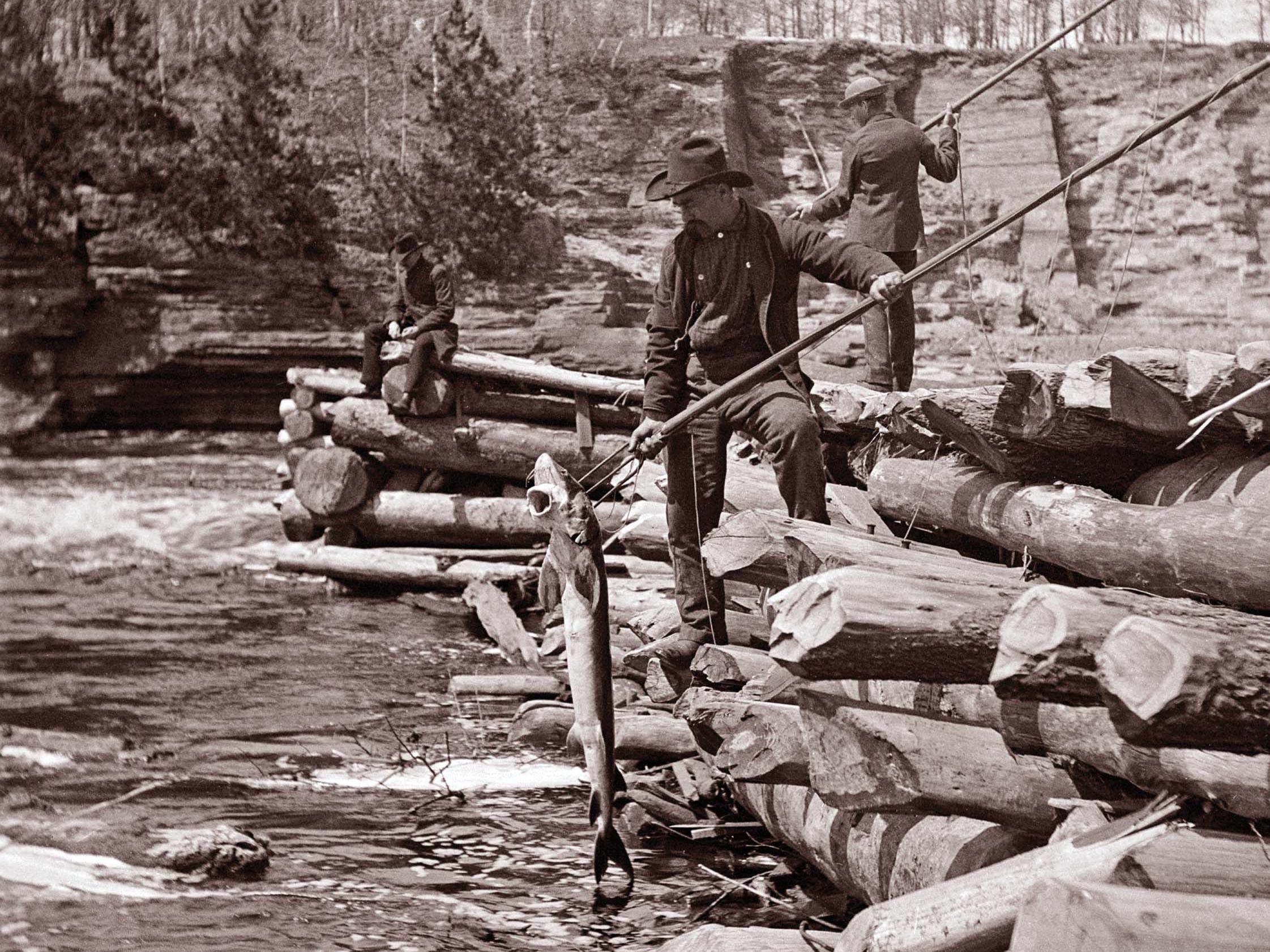 Men spear sturgeon at the dame in Kilbourn (now Wisconsin Dells).  (Photo ID 7287)