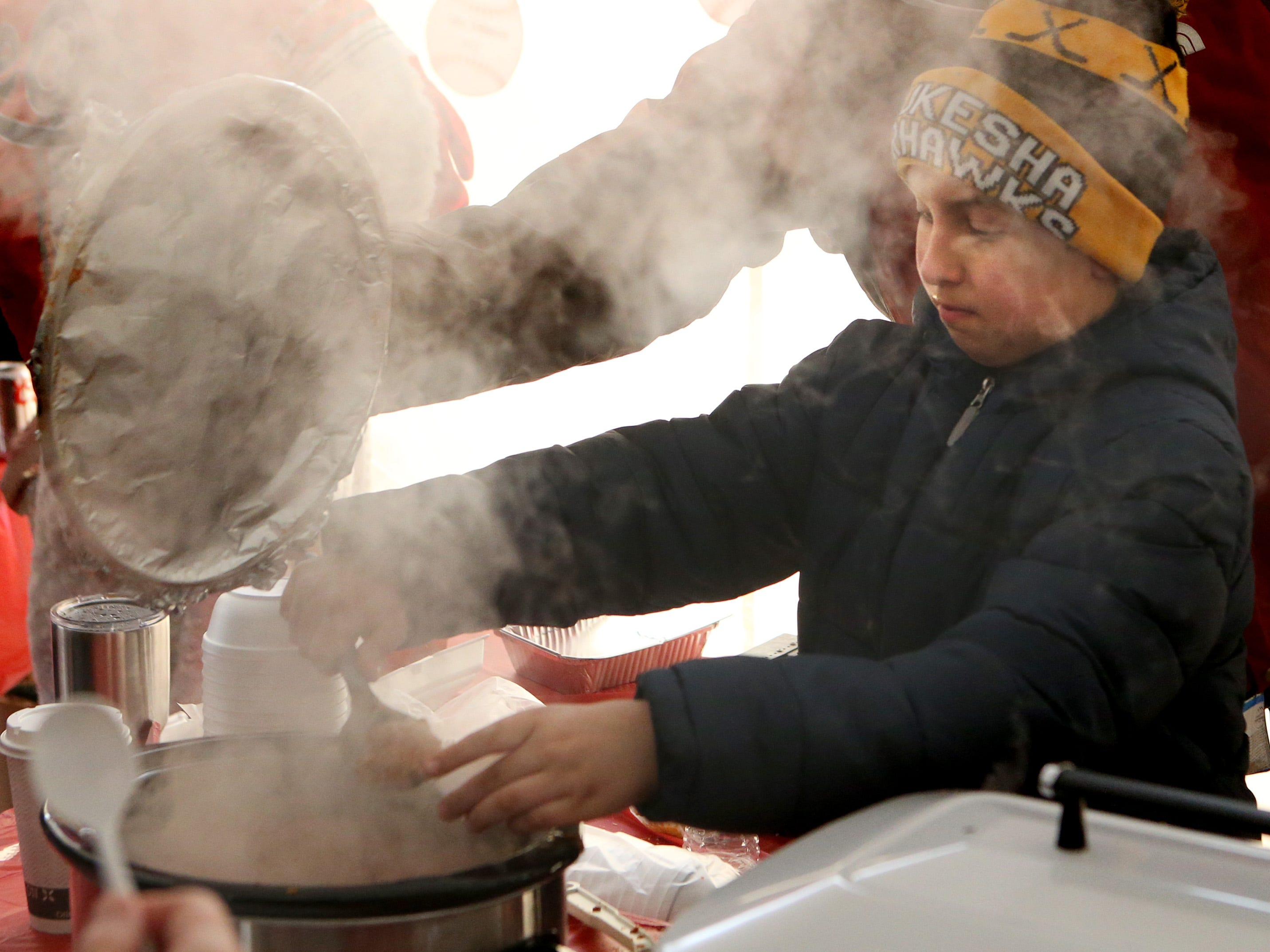 Steam swirls around Luke Belawski as he scoops up a portion of Buffalo Chicken Chili offered by the 5 O's U11 baseball team Cook Off tent where 11 non-profit groups offered different takes on the classic winter fare during Oconomowoc's Chili Fest on Jan. 26.