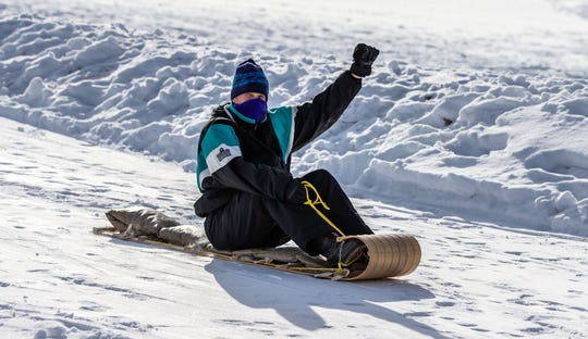 Erik Swenson of Dousman celebrates a successful ride down the Arctic Avalanche toboggan run at Lowell Park in Waukesha during the 34th annual Waukesha JanBoree on Sunday, Jan. 27, 2019. The three-day family friendly extravaganza features 39 individual events throughout the city.
