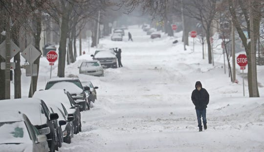 A man walks in blowing snow along North 26th Street near West Kilbourn Avenue.