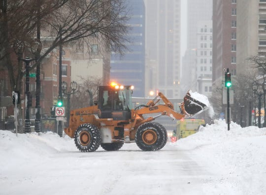 A plow removes snow along West Wisconsin Avenue at North 8th Street in Milwaukee.