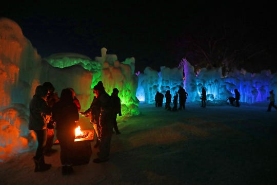People huddle around a fire as LED lights illuminate the ice formations at the Ice Castles display in Lake Geneva. The Ice Castles, which opened up last week in Lake Geneva, are among six cities across North America where a Utah-based company has built ice castles after growing 5,000 to 12,000 icicles harvested by hand and individually sculpted into ice formations. Newly placed icicles are then drenched with water. Each castle is around one acre in size and takes around two months to construct by 20 to 40 ice artisans.