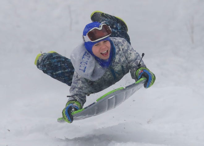 Andrew Elliott, 12, a Whitefish Bay Middle School seventh-grader off from school for a snow day, gets airborne on a jump while sledding at Kletzsch Park in Glendale. Some school districts will have virtual learning days in place of the traditional snow day.