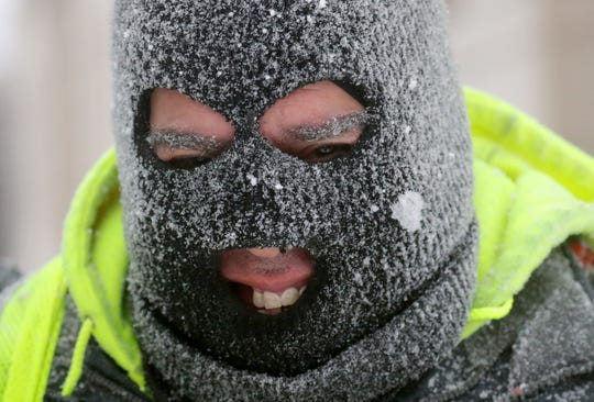 Robert Delgado smiles through his snow-covered ski mask while shoveling Monday in front of the Milwaukee Public Library on West Wisconsin Avenue at North 8th Street in Milwaukee.