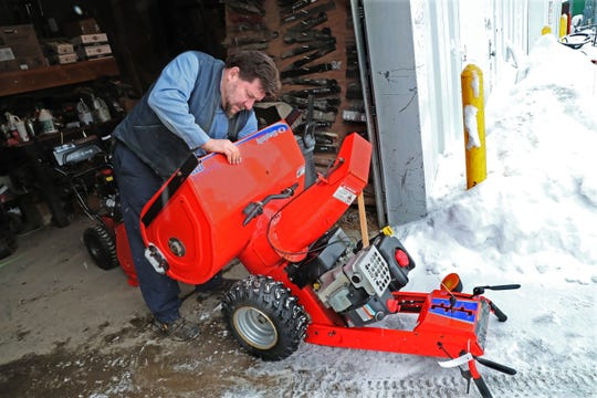 Fred Schmitter, a repair technician at Lorleberg True Value Hardware in Oconomowoc, searches for the source of the problem with a snowblower brought in for repair Monday. The owner said it ran poorly and had a bad smell, probably from a slipping drive belt.