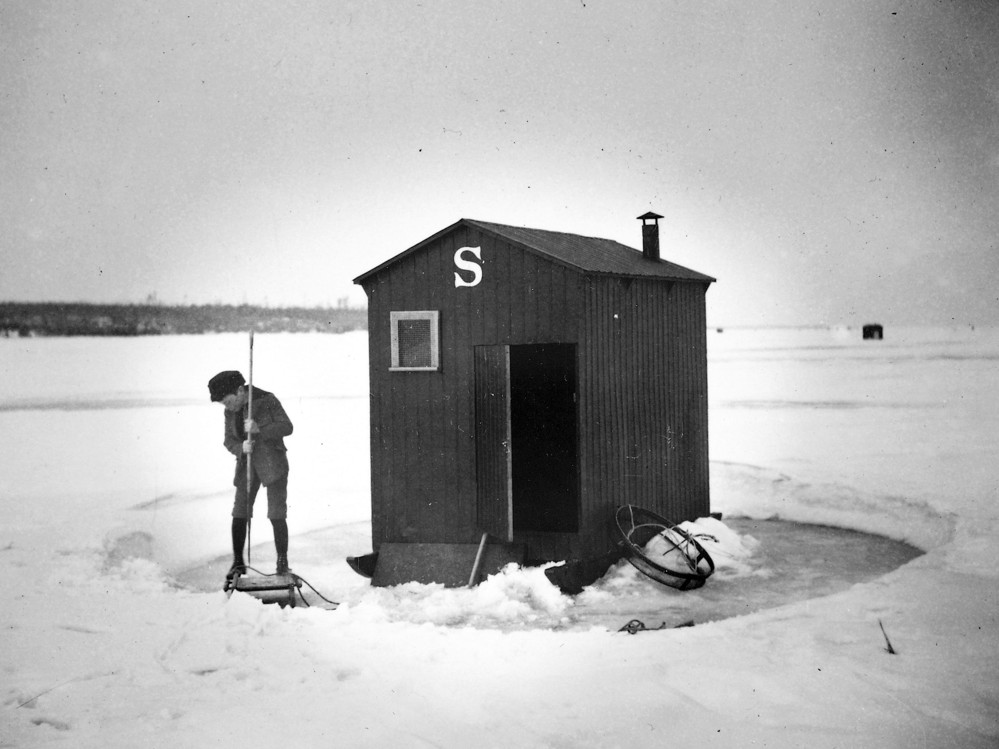 In 1898, a boy clears the ice around his family's ice shanty in preparation to fish. (Photo ID 24511)