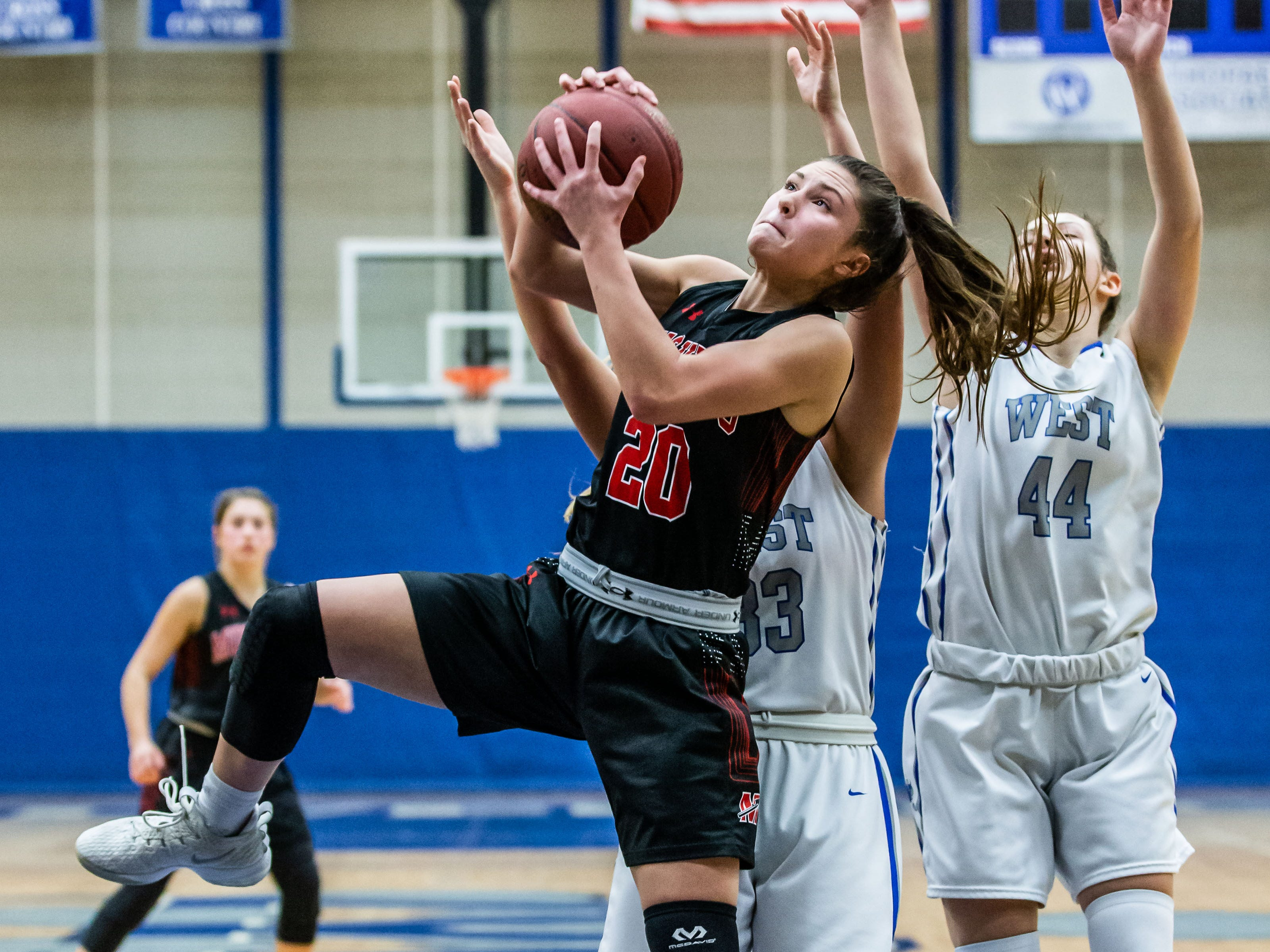 Muskego's Savanah Balcerak (20) pulls down a rebound during the game at Waukesha West on Friday, Jan. 25, 2019.