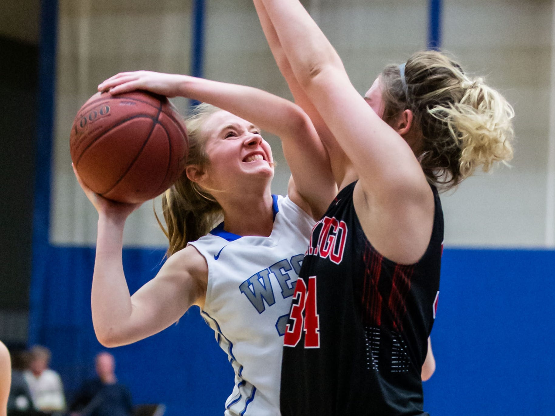 Waukesha West's Emily Rather (left) is blocked by Muskego's Kenni Czarnecki (34) during the game at Waukesha on Friday, Jan. 25, 2019.