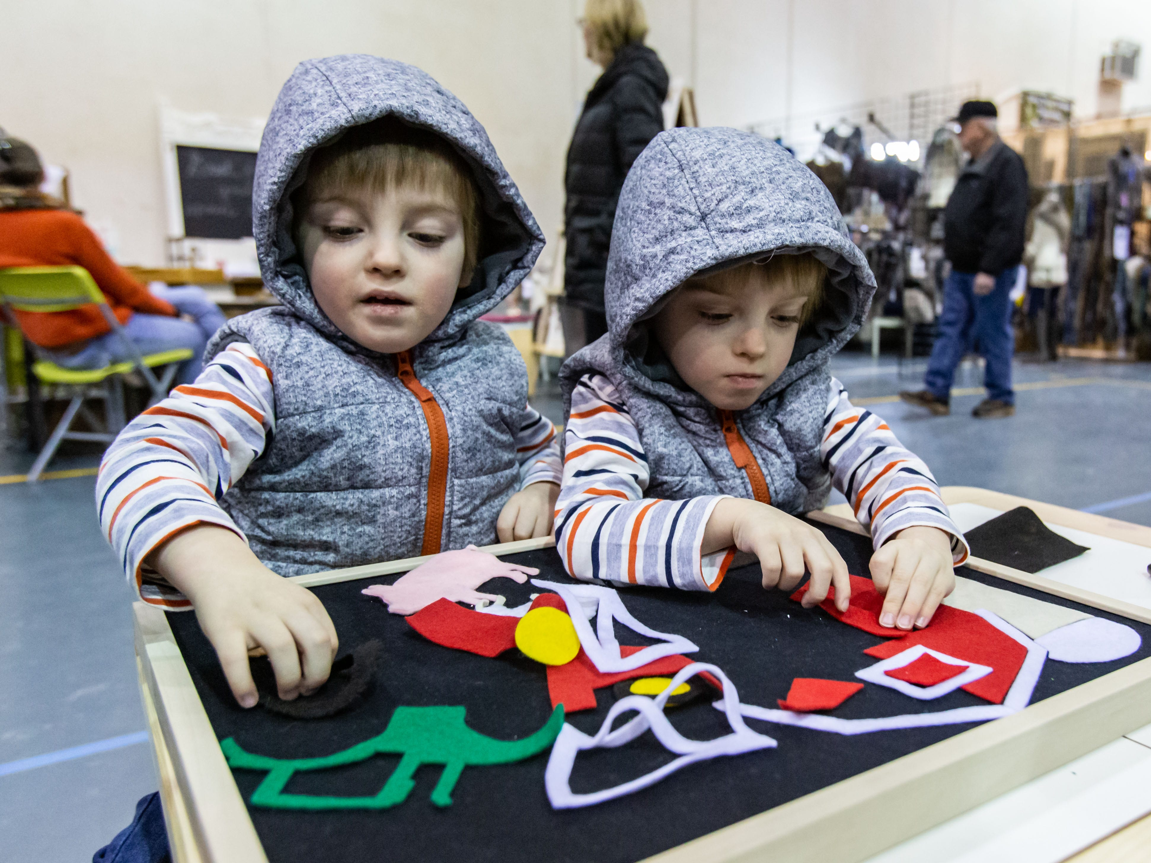 Three-year-old twins, Arthur (left) and Oliver Mooney of Port Washington, play a game from Drift & Row during the re:Craft and Relic show at the Milwaukee County Sports Complex in Franklin on Sunday, Jan. 27, 2019. Milwaukee based Drift & Row offers a handmade collection of toys and games that support language and learning.