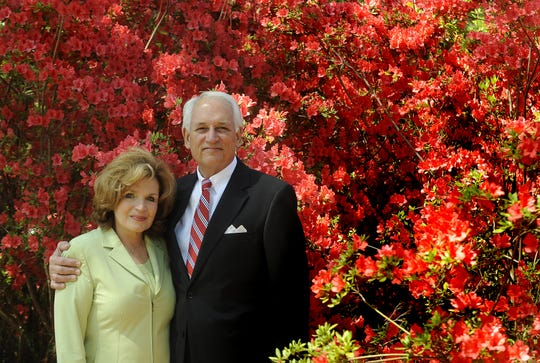 Troy University chancellor Jack Hawkins and his wife Janice Hawkins pose with blooming azaleas at their home in Troy.