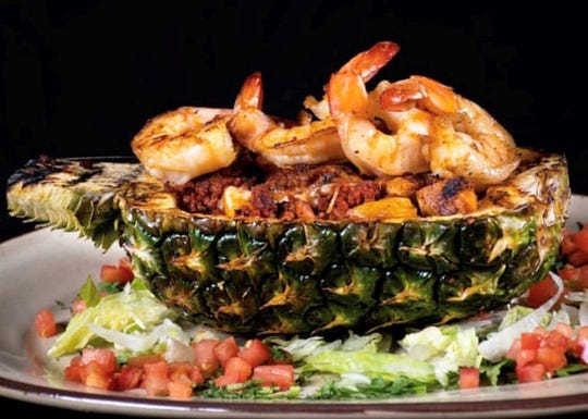 The Hawaiian fajitas include chicken, shrimp and bacon with pineapple chunks and mozzarella cheese served in a grilled pineapple shell at El Meson Latin Cuisine Bar & Grill in Bonita Springs.