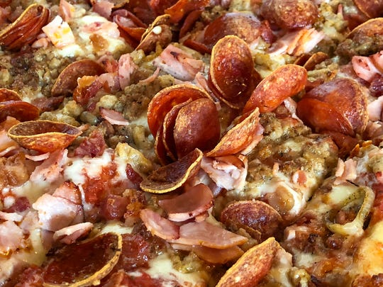 The meat lovers pizza at The Crust is topped with pepperoni, sausage, meatball bacon and ham.