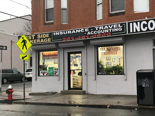 """West Side Brokerage in Jersey City removed mentions of """"immigration services"""" from its awning. The storefront glass still mentions """"immigration forms,"""" but owner Meriem Hanno said she is trying to remove the language."""