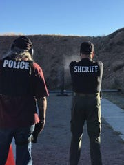Doña Ana County Sheriff's Department deputy and rangemaster John Paul Duffy, left, watches as DASO investigator Bo Nevarez fires a weapon. Duffy died by suicide Friday, Jan. 25, 2019.