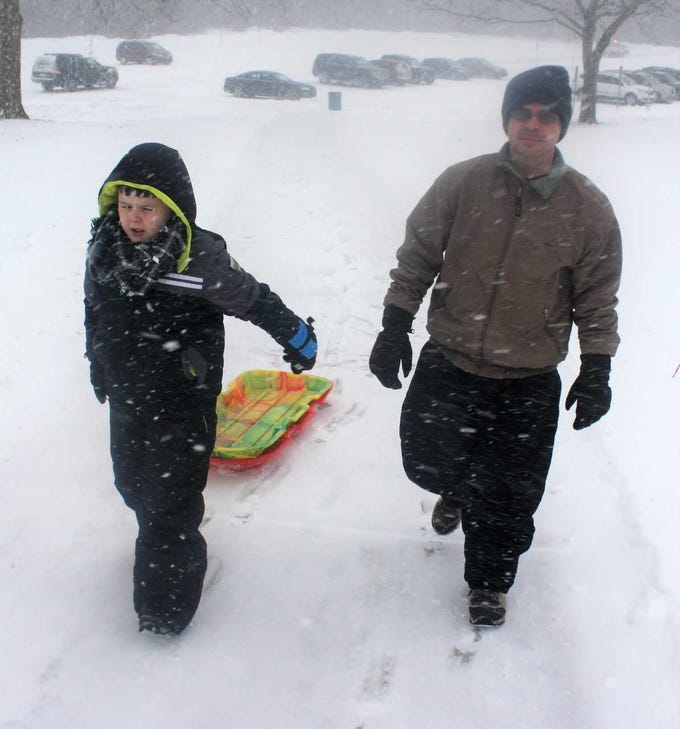 Jackson and Stan Jogodzinski head from the parking lot to the sledding hill at McClumpha Park.