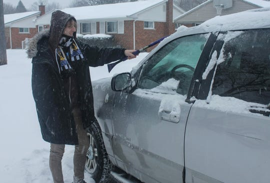 Livonia resident Dominic Petro clears snow off his car Monday afternoon.