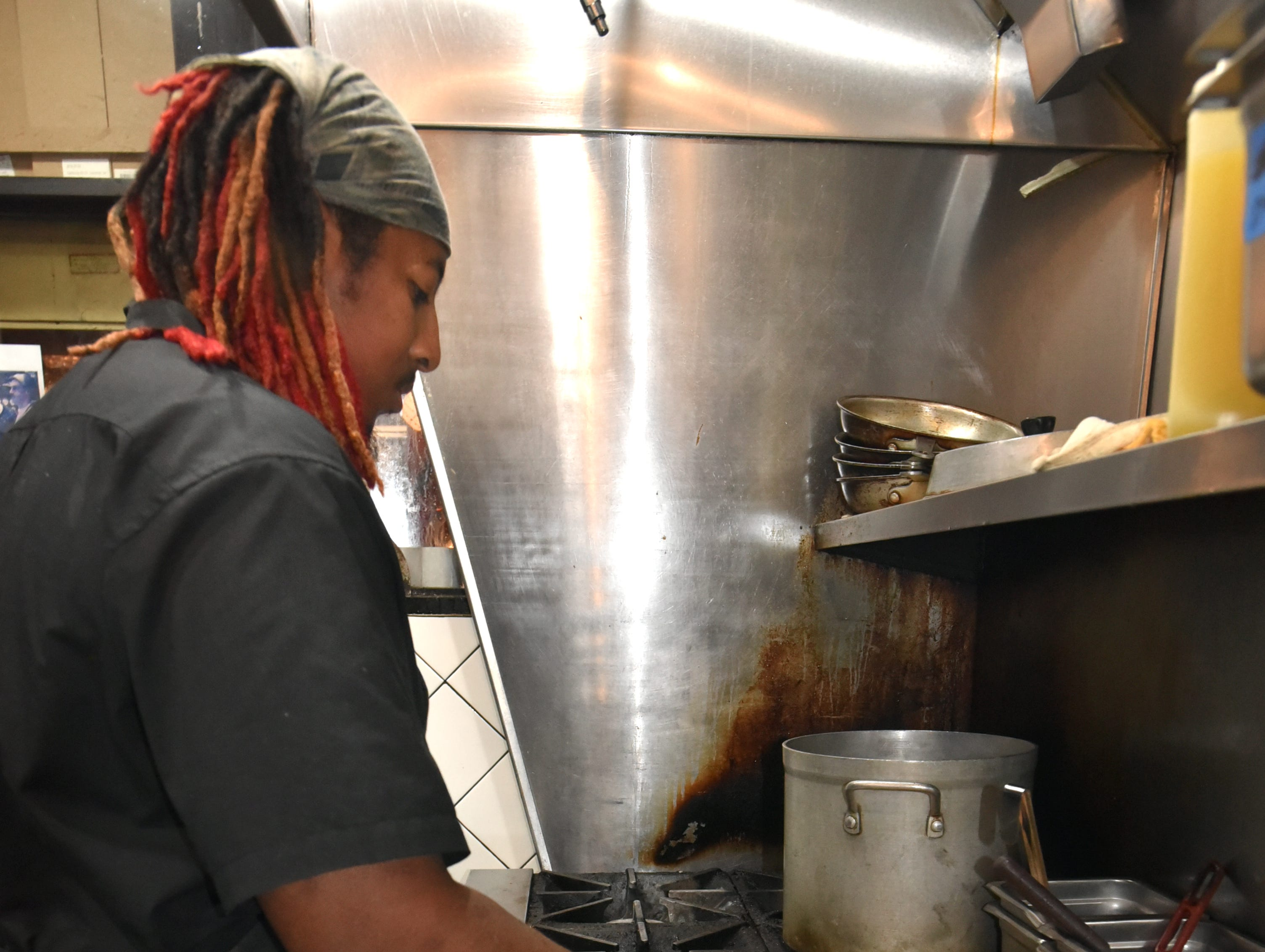 Birmingham restaurant chef Raphel Martin prepares one of his kitchen's specialties: a Cubano sandwich with ham, bacon, grill-toasted bread, pickles, and cabbage.